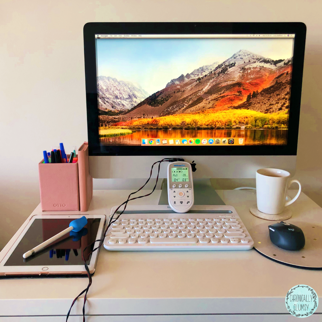 """Photograph of a computer desk, with a pink pen-holder and A5 diary on the rear left corner, an iMac computer displaying a mountain range desktop at the back of the desk in the centre, and a cup of tea in a white mug just in front of the computer on the right. In the foreground, there is a black mouse on a pink and gold mousepad, a white keyboard, a TENS machine with a green screen perched on top of the keyboard with it's wires trailing off the front of the desk, and an iPad with an apple pencil on top of the black screen, with a blue ergonomic pencil grip. The Chronically Clumsy logo is in the bottom right corner of the image - a blue circle with a wreath of leaves surrounding the words """"Chronically Clumsy"""""""